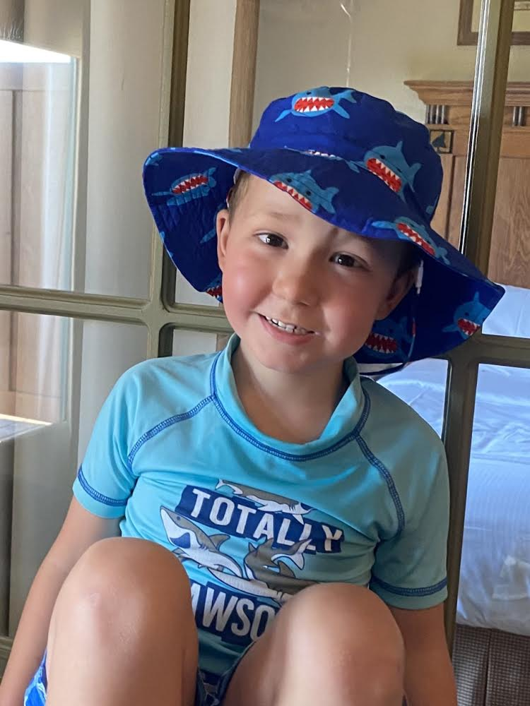 young boy who is happy with sun hat on