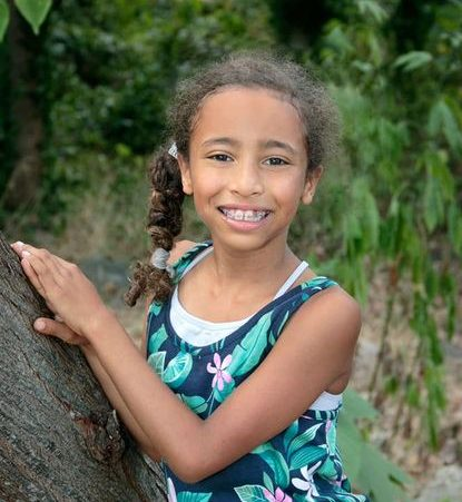 Young girl named Alexandra leaning on a tree with a big smile